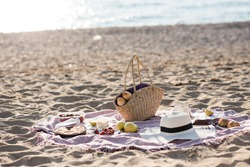 Having picnic with fresh bread, straw bag and hat on blanket at sandy beach over sea shore at background. Summer season. Vacation time.