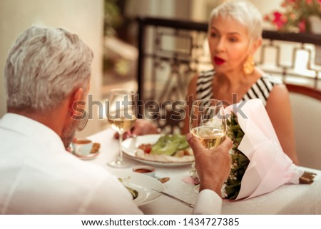 Having romantic dinner. Couple of mature man and woman having romantic dinner at the weekend