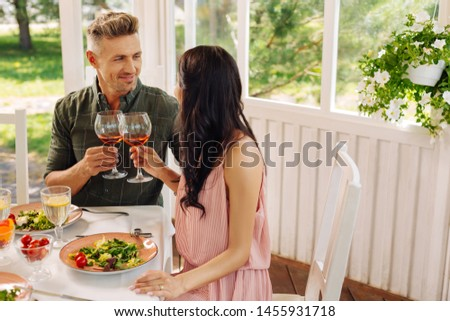 Having romantic lunch. Couple having romantic lunch in summer house eating salads and drinking wine