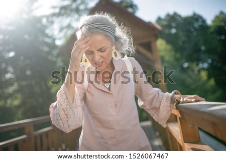 Having strong headache. Grey-haired mature woman wearing nice earrings having strong headache