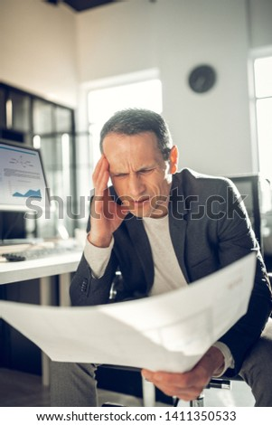 Having strong headache. Mature hard-working interior designer looking at sketches having strong headache