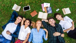 Having the best time with friends. Top view of a group of students lying on the grass enjoying their break.