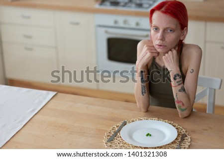Having unhealthy look. Tattooed red-haired woman suffering from anorexia having unhealthy look #1401321308