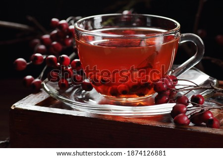 Haw thorn berry tea ina  glass cup, red herbal tea is a sedative relaxing hot drink against heart disease, insomnia, neurosis and hypertension, closeup, copy space, naturopathy concept