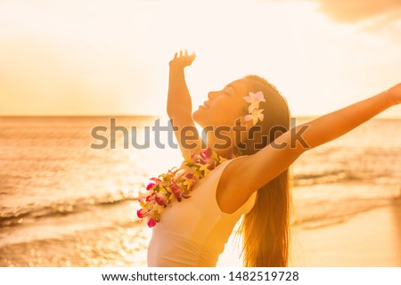 Hawaii beach sunset Asian woman in sun glow sunset with arms outstretched up dancing in hula luau party enjoying hawaiian vacation
