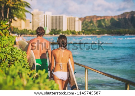 Hawaii beach surfing lifestyle. Young surfers people walking with surfboards on Waikiki beach tourists on summer travel vacations.