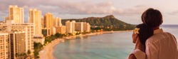 Hawaii couple panoramic vacation travel tourists at Honolulu hawaiian resort hotel banner panorama. Happy man and woman relaxing at sunset view of Diamond Head, Oahu island.