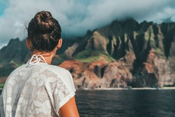 Hawaii cruise woman from behind looking at sea level view of Na Pali Coast with dramatic cliffs mountain landscape. Kauai island tourist travel destination, USA.