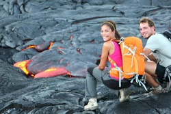 Hawaii lava tourist on hike. Tourists hiking near flowing lava from Kilauea volcano around Hawaii volcanoes national park, USA. Multiethnic couple.