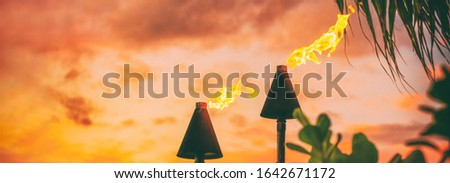 Hawaii Luau Tiki fire torches for hawaiian party celebration panorama banner at sunset.