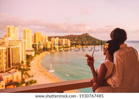 Hawaii luau vacation Mai Tai drink cocktail couple tourists at Honolulu hawaiian resort hotel. Happy man and woman relaxing at sunset view of Diamond Head, Oahu island travel.