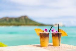 Hawaii mai tai drinks on waikiki beach bar travel vacation in Honolulu, Hawaii. Famous hawaiian drink cocktails with view of ocean and diamond head mountain, Hawaii tourist attraction.