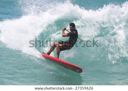 HAWAII - MARCH 15: Stand Up Paddle surfing has become very popular over the past few years, this surfer performs a powerful cutback March 15, 2009 at Ehukai Beach, Hawaii. - stock photo