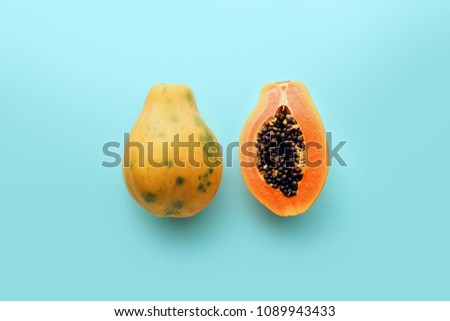 Hawaii papaya on a pastel blue background, creative food concept, tropical fruit flat lay