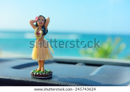 Hawaii road trip - car hula dancer doll dancing on the dashboard in front of the ocean. Tourism and travel freedom concept. - stock photo