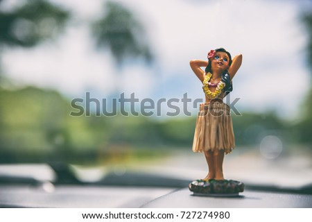 Hawaii road trip - car hula dancer doll dancing on the dashboard in front of the ocean. Tourism and travel freedom concept.