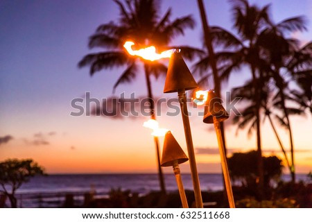 Hawaii sunset with fire torches. Hawaiian icon, lights burning at dusk at beach resort or restaurants for outdoor lighting and decoration, cozy atmosphere.