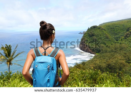 Hawaii travel nature hiker girl hiking in Pololu valley enjoying lookout view of mountains. Big island destination, woman tourist in Hawaii, USA.