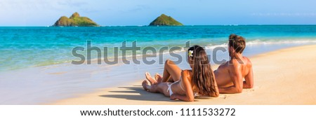 Hawaii travel summer vacation couple on hawaiian tropical beach in Lanikai, Oahu, Hawaii, US. American tourists people on holidays lying down, panoramic banner crop with moke islands in background.