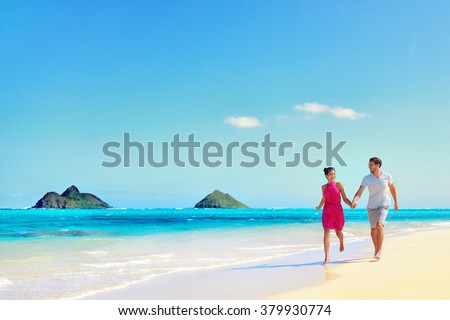 Stock Photo Hawaii vacation couple walking relaxing on white sand and pristine turquoise ocean water on Hawaiian beach Lanikai, Oahu island, USA. Holiday background with blue sky copy-space for travel concept.