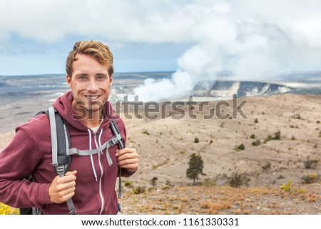 Hawaii volcano tourist man at Halemaumau crater in Kilauea caldera in Hawaii Volcanoes National Park, big Island with volcanic clouds and ash from eruption.