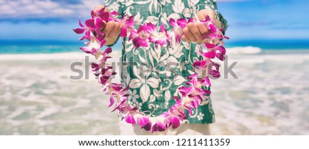 Hawaii welcome hawaiian lei flower necklace offering to tourist as welcoming gesture for luau party or beach vacation. Polynesian tradition.