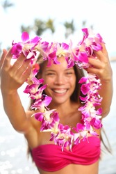 Hawaii woman showing flower lei garland of pink orchids. Beautiful smiling mixed race woman in bikini on beach giving a welcoming Lei on the hawaiian island Big Island.