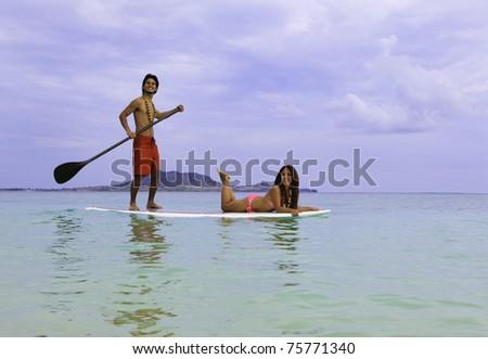hawaiian beachboy with girl in bikini on paddle board in hawaii