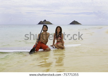 hawaiian beachboy with girl in bikini on paddle board in hawaii