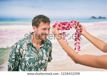 Hawaiian lei flower garland necklace welcome gesture of giving orchids welcoming tourist on Hawaii beach. Happy man receiving traditional gift on summer tropical holidays.