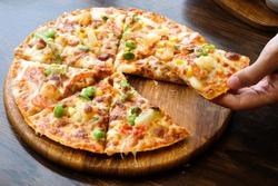 Hawaiian Pizza lifted slice on wooden table