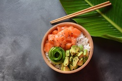 Hawaiian Salmon Poke Bowl with  avocado, cucumber , rice and sesame seeds served in bowl on tropical leaves. Sushi bowl.Organic and healthy food.