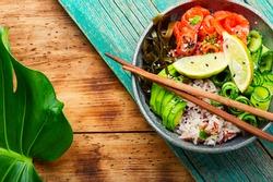 Hawaiian salmon poke bowl with rice,seaweed and avocado