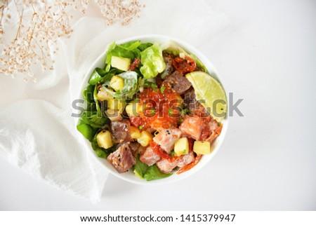 Hawaiian salmon poke bowl with roes, avocado, and lemon. Poke bowl flat lay. Healthy eating raw food, raw fish. Sashimi poke on white table. Poke bowl with copy space.