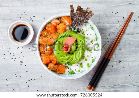 Hawaiian salmon poke bowl with seaweed, avocado rose, sesame seeds and scallions. Top view, overhead, flat lay - Shutterstock ID 726005524
