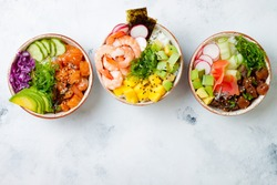 Hawaiian salmon, tuna and shrimp poke bowls with seaweed, avocado, mango, pickled ginger, sesame seeds. Top view, overhead, flat lay, copy space