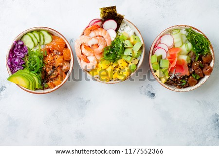 Hawaiian salmon, tuna and shrimp poke bowls with seaweed, avocado, mango, pickled ginger, sesame seeds. Top view, overhead, flat lay, copy space #1177552366