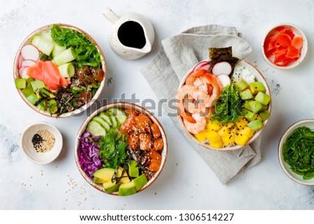 Hawaiian salmon, tuna and shrimp poke bowls with seaweed, avocado, mango, pickled ginger, sesame seeds. Top view, overhead, flat lay #1306514227