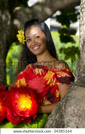 Hawaiian teenage girl leaning on a tree and smiling