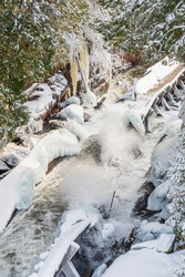 Hawk Lake Log Chute Historical Conservation Area Haliburton County Algonquin Highlands Ontario Canada in winter featuring frozen two century old log chute with lots of icicles and rushing water