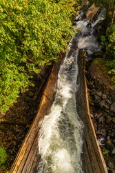 Hawk Lake water chute  in Ontario Canada featuring water streaming down century old wooden chute with forest on a sunny autumn day