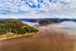 Hawkesbury river flowing to Pacific ocean in Greater Sydney area connected by railway bridge from Long Island to the Central coast. Aerial view on a sunny day.