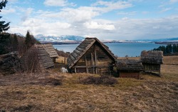 Hay hut in the pasture in front lake and high mountains in background. Spring warm weather. An abandoned vikings village. Sod rooftops, turf rooftops.