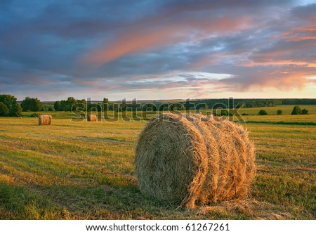 Hay rolls and dramatic sunset.