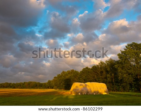 hay stack during sunset with dramatic cloudy sky #86102299