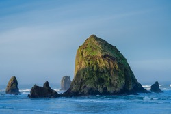 HAY STACK ROCK IN CANNON BEACH OREGON WITH EARLY MORNING LIGHT AND SHADOWS