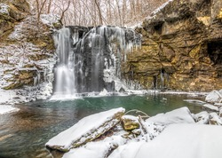 Hayden Run Falls, a secluded waterfall in Columbus, Ohio, is surrounded by winter snow with icicles freezing on rock walls.