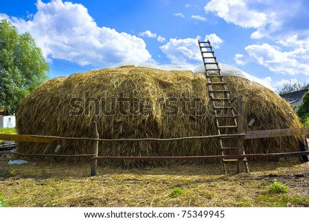 haystack against the backdrop of blue sky with clouds