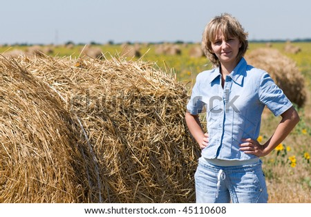 Haystack and girl on meadow in sunny day