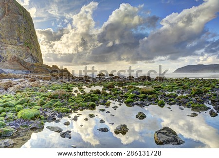 Haystack Rock with evening back lighting at low tide, Cannon Beach, Oregon. A large tide pool is in foreground with partly cloudy sky reflection. HDR fusion image. Warning sign on rock edited out..